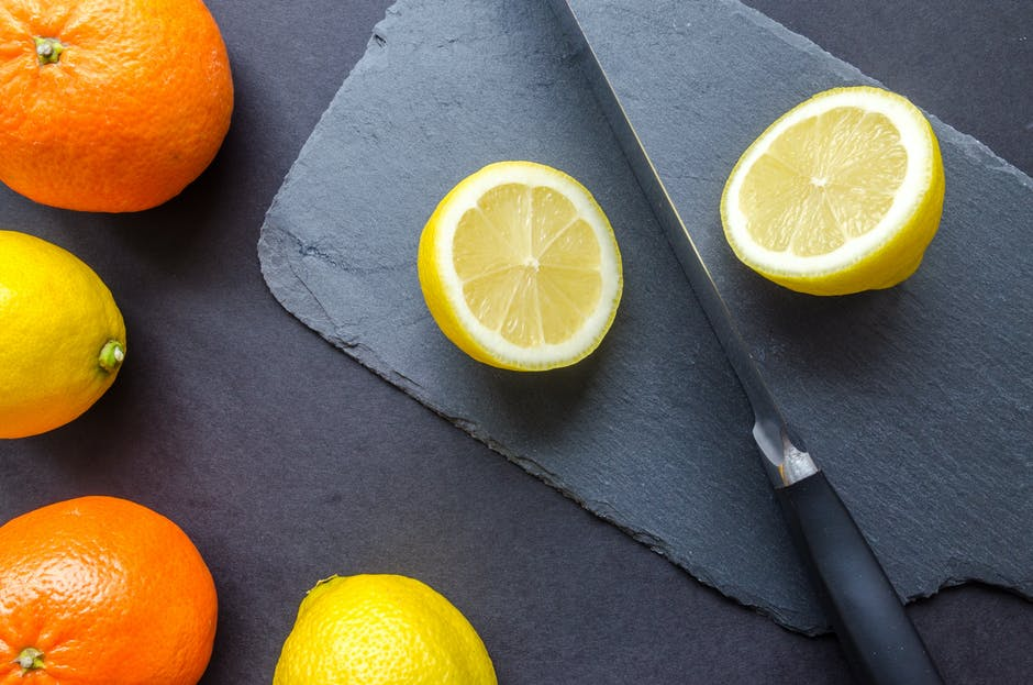 Two Orange and Three Lemons on Gray Surface