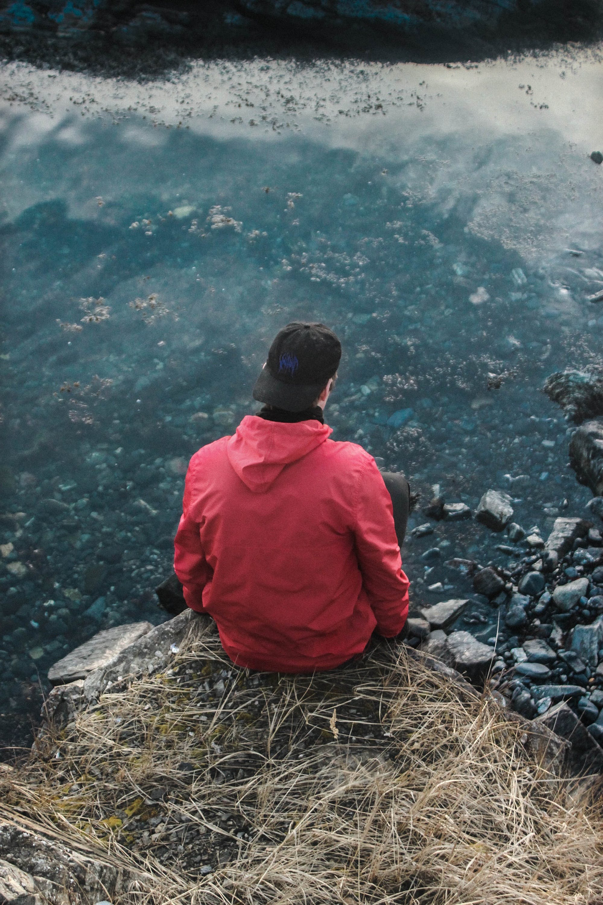 Man in Red Hoodie Sitting on Cliff