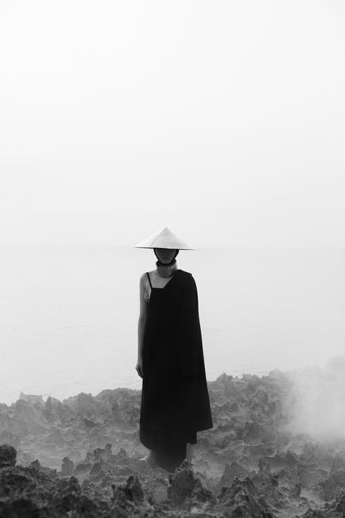 Person in Black Coat Standing on Rock Formation