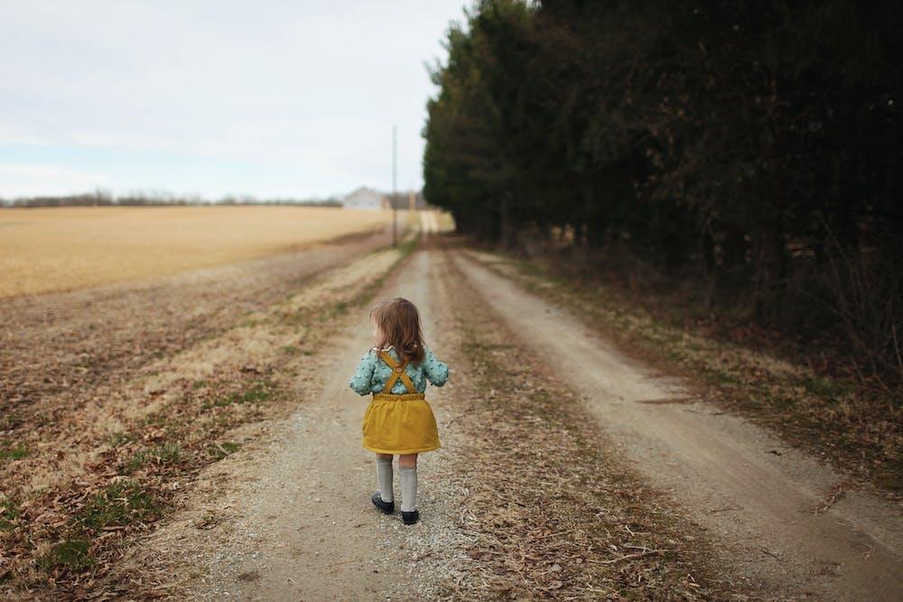 Mädchen läuft Feldweg hinunter | Quelle: Pexels