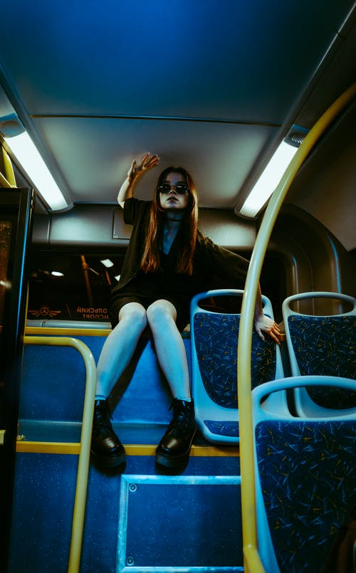 Woman in Black Long Sleeve Shirt and Blue Denim Jeans Sitting on Blue and White Train