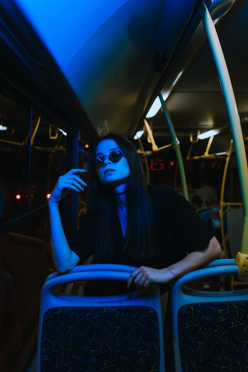 Woman in Black Long Sleeve Shirt Wearing White Mask Sitting on Blue and Black Vehicle Seat