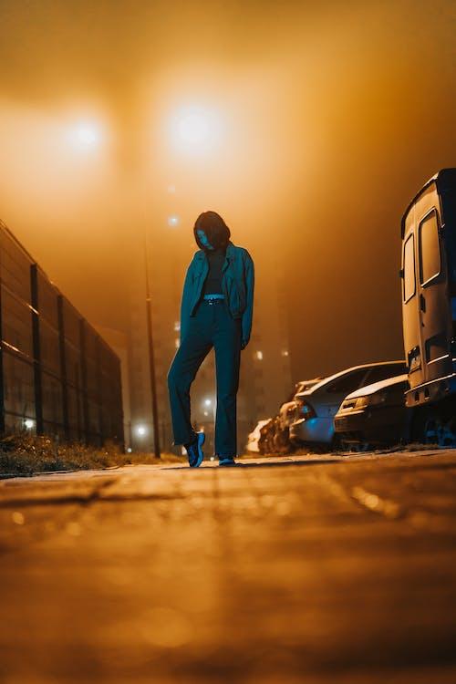 Man in Blue Jacket and Blue Denim Jeans Standing Beside White Van