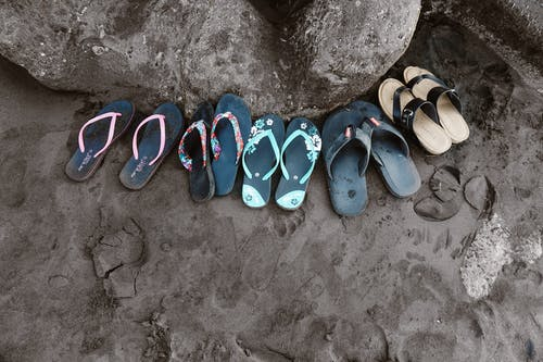 Assorted Flip-flops on Sand