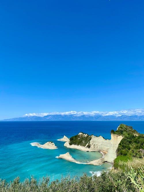 Cliff View of Ocean Water Under Blue Sky