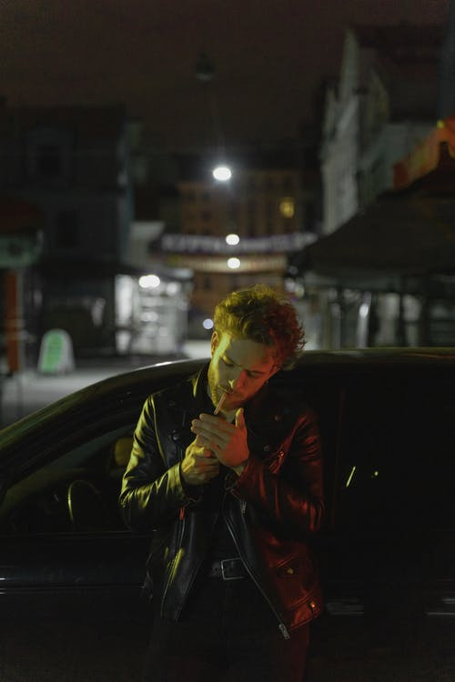 Man in Black Leather Jacket Standing Beside Black Car during Night Time