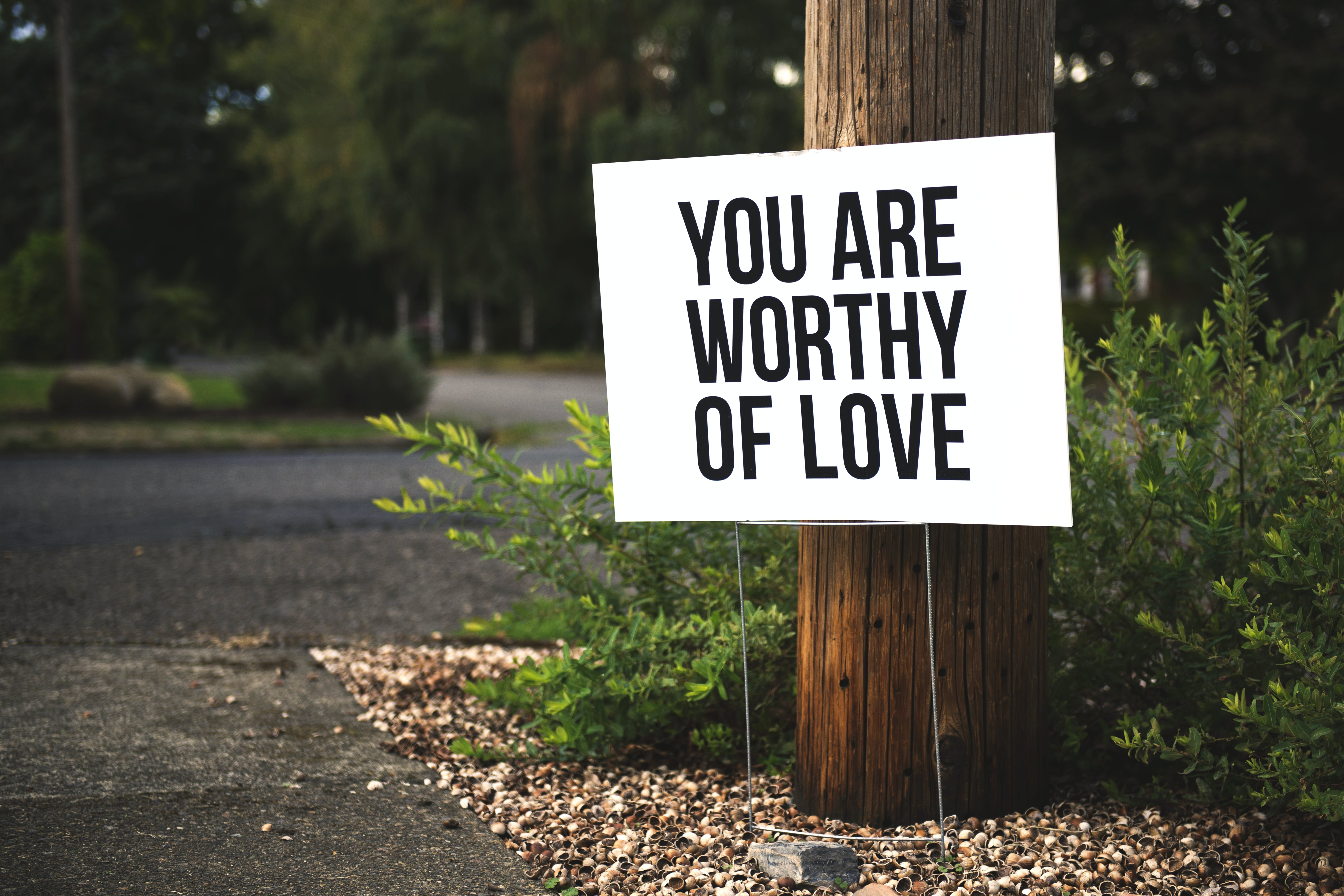 You Are Worthy of Love Signage on Brown Wooden Post Taken