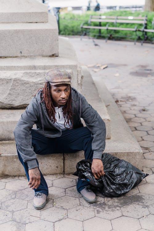 Gratis stockfoto met Afro-Amerikaanse man, andere kant op kijken, armoe
