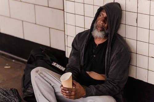 Man in Black Hoodie Holding White Ceramic Mug