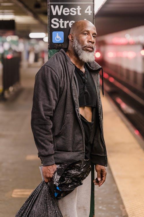 Man in Black Zip Up Jacket Standing on Sidewalk