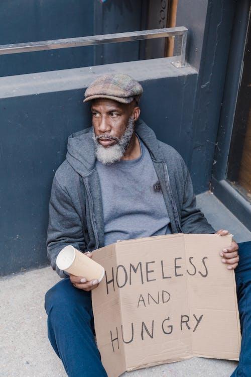 Uomo Seduto Su Un Marciapiede Con Un Cartello Di Senzatetto E Affamato
