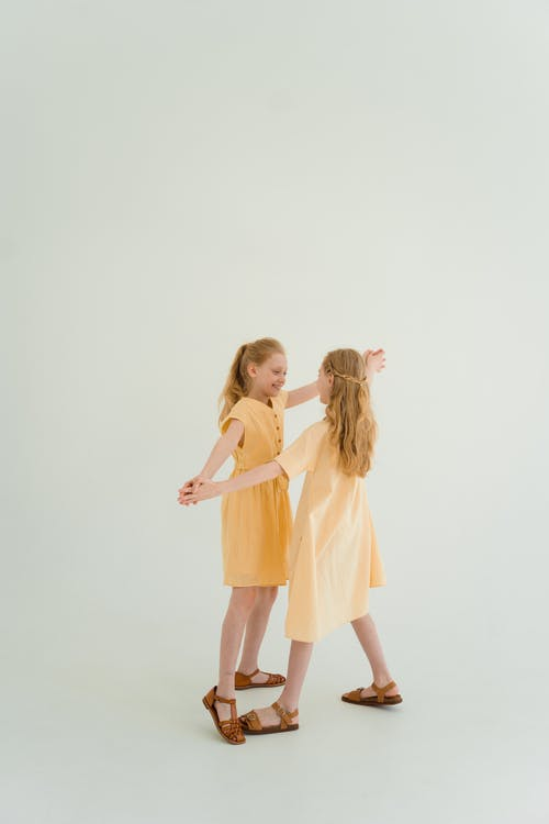 Two Beautiful Girls Holding their Hands and Dancing