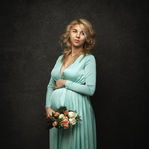 Photo of a Pregnant Woman in a Teal Dress Holding a Bouquet of Flowers