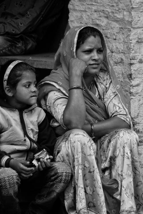 Grayscale Photo of a Mother Sitting Beside Her Daughter