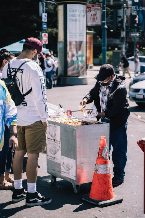 Man in White Shirt and Black Hat Standing in Front of Food Stall
