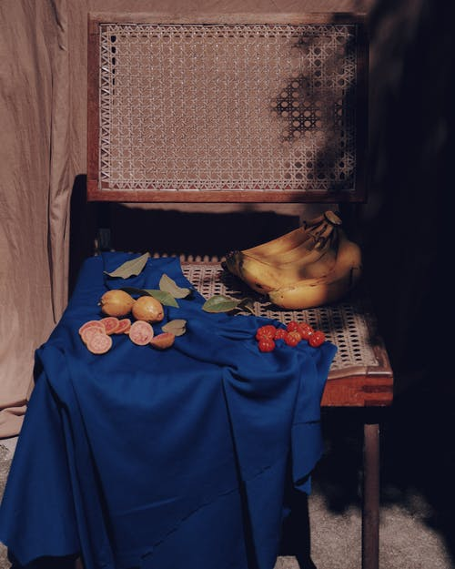 Woman in Blue Hijab Standing Near Fruits on Table