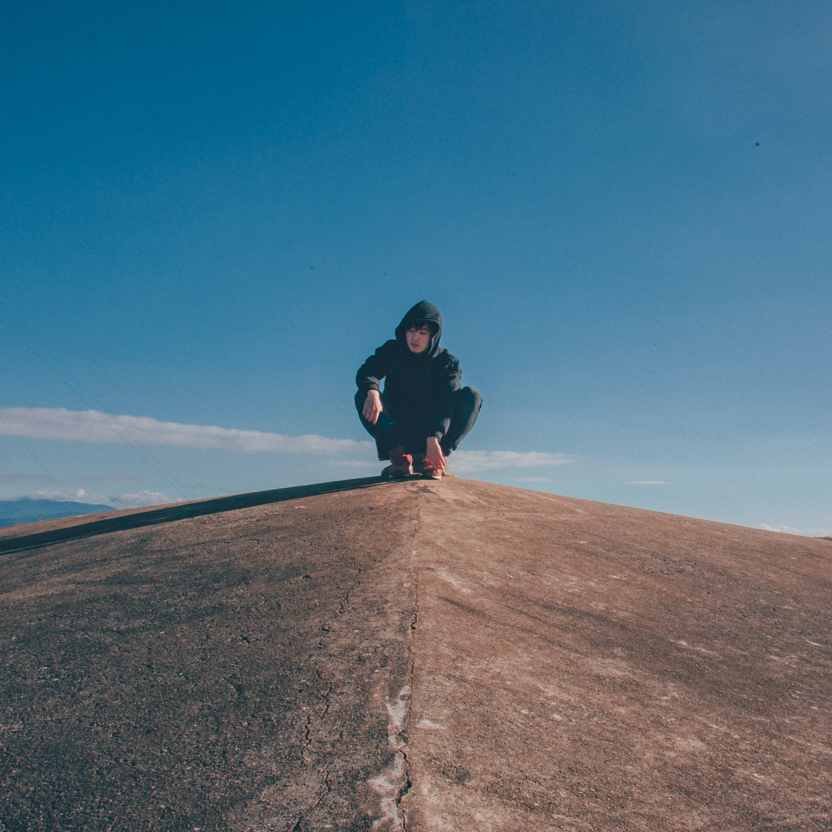 Man in Black Hoodie and Pants Sitting on Top of Rocky Cliff