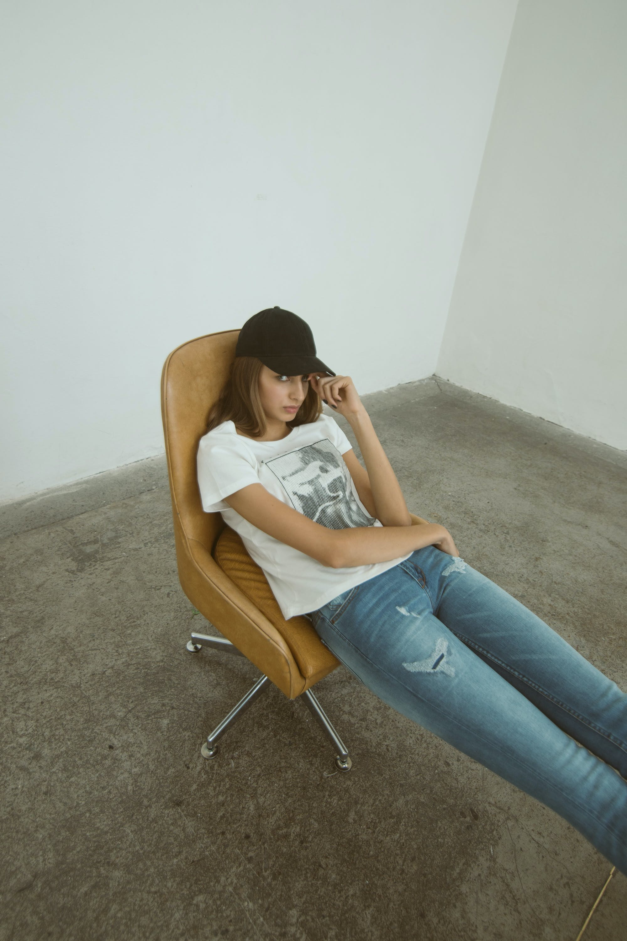 Woman Wearing White Printed Shirt Sitting on Brown Leather Rolling Chair