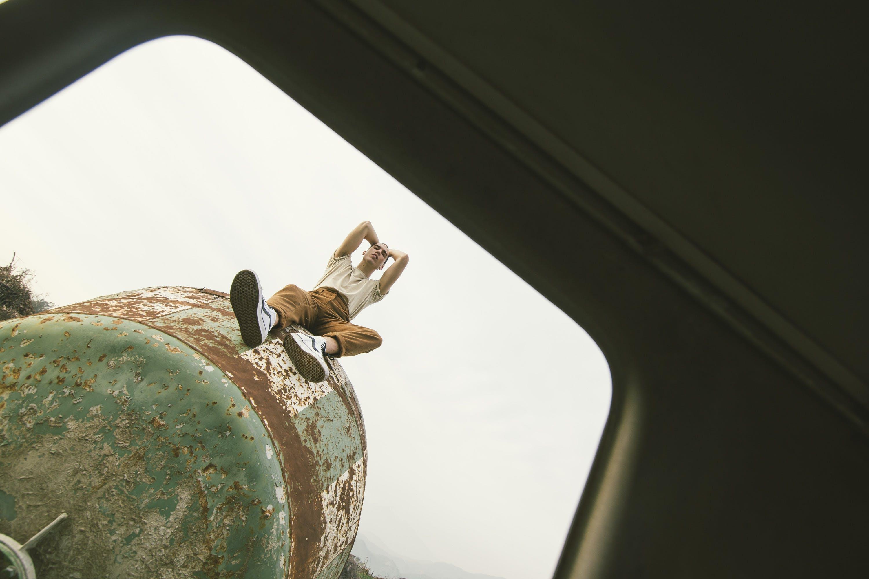 Person Sitting on Green Metal Tank