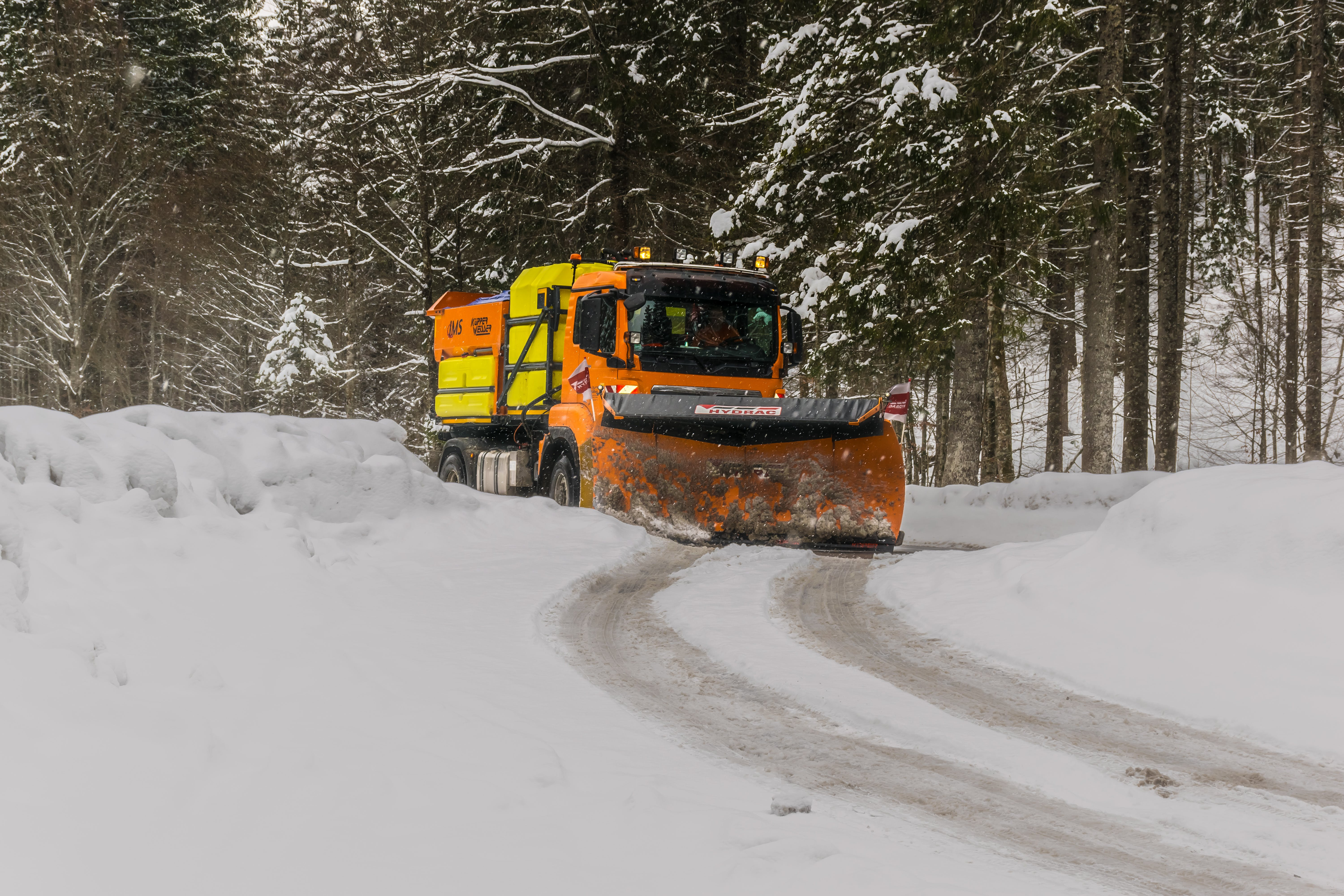 Yellow, Orange, and Black Truck Plowing Snow