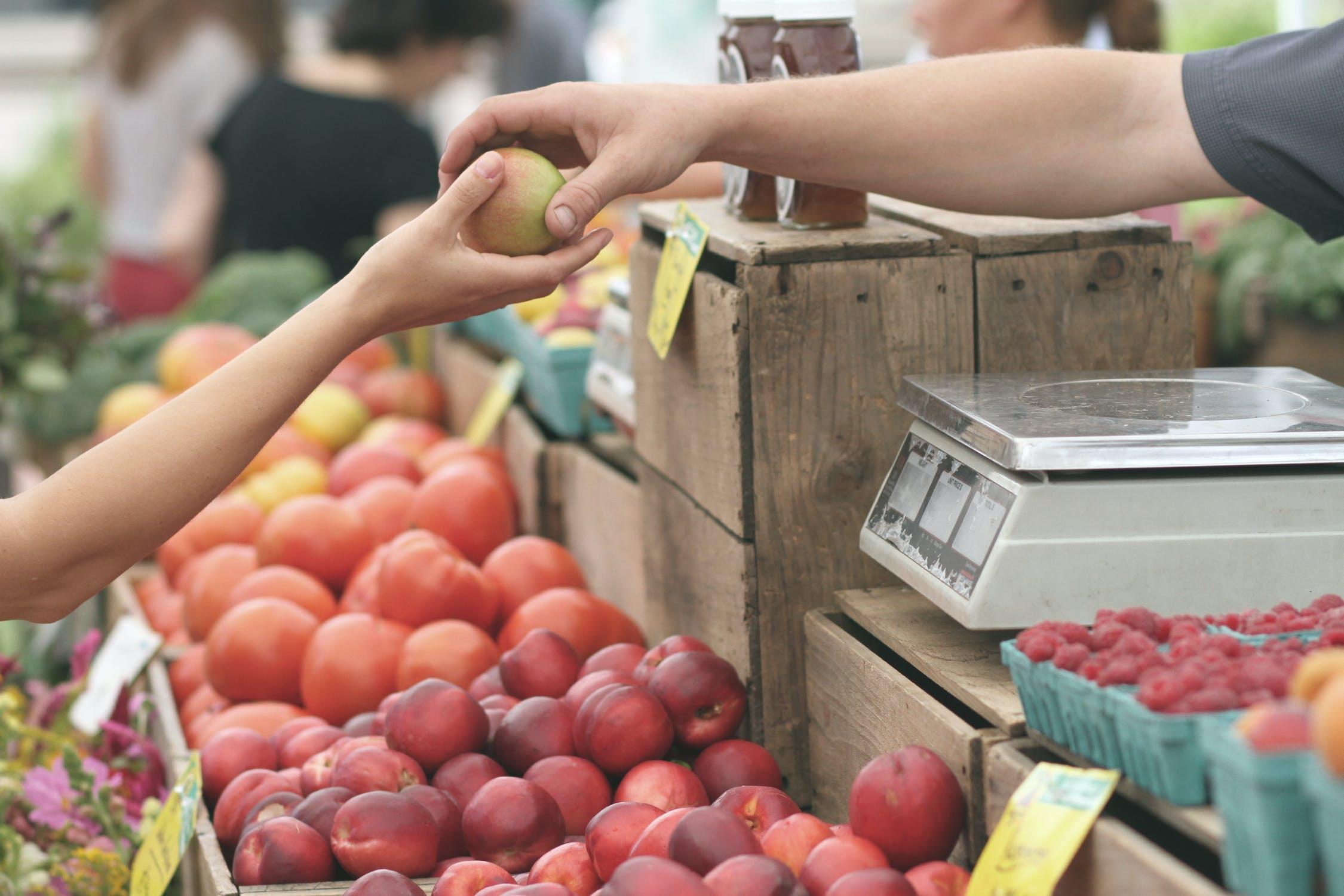 Person reicht dem Verkäufer eines Marktstandes einen Apfel zum Bezahlen
