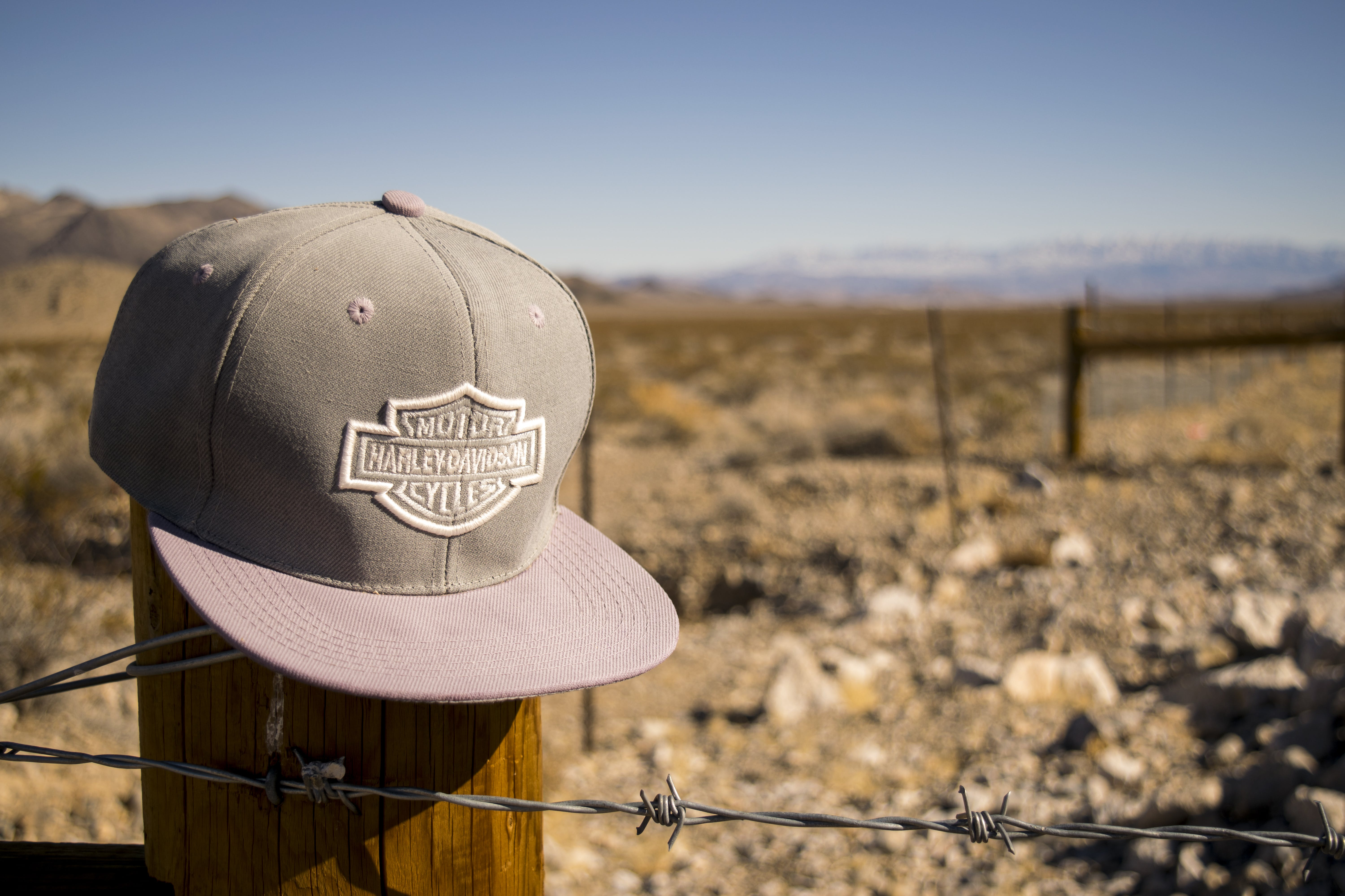 Gray Harley-davidson Motorcycles Flat-brimmed Cap Hanged on Brown Wooden Fence With Gray Barb Wires
