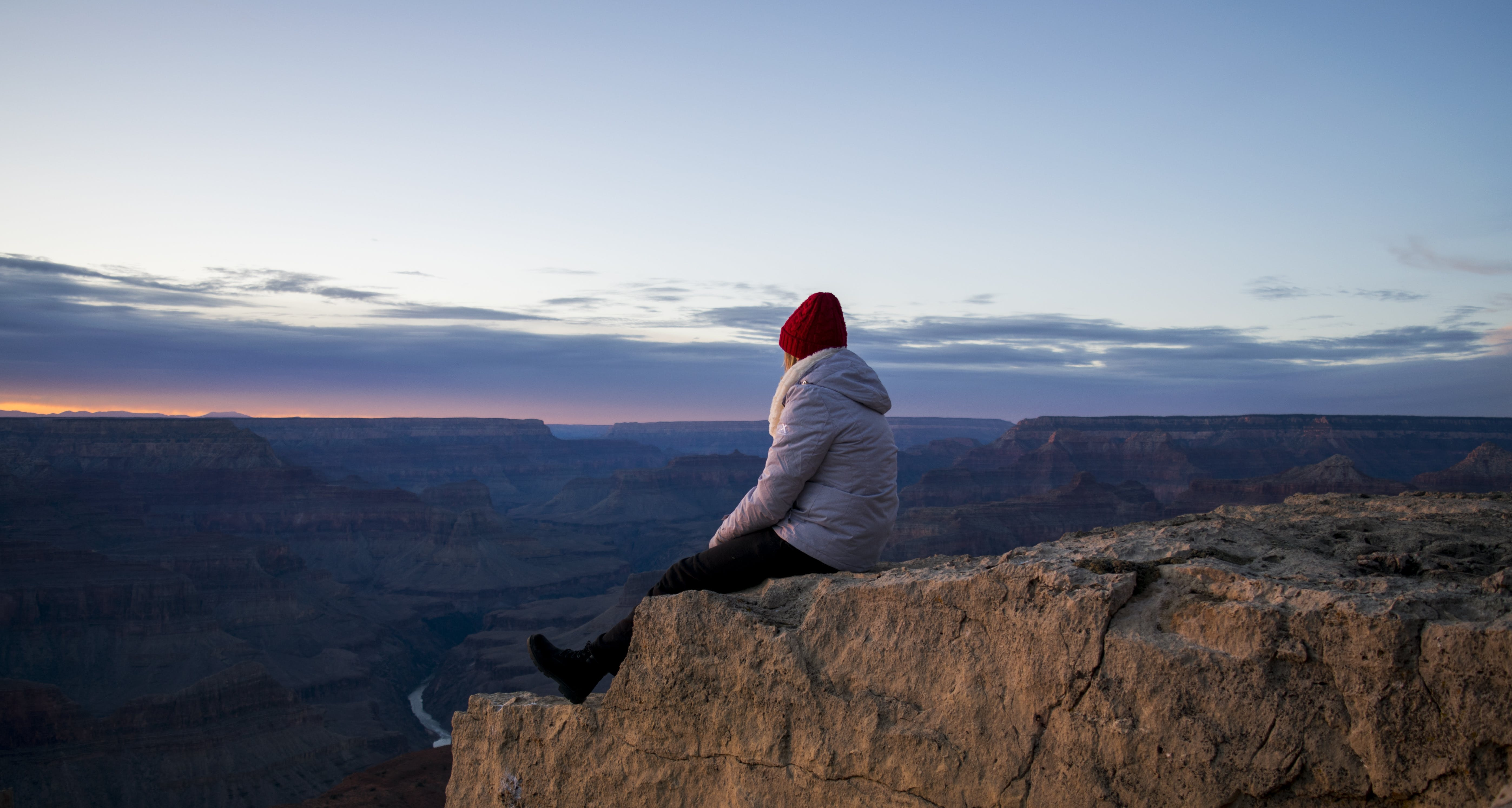 Person Wearing Gray Hooded Jacket and Black Pants Sitting on Mountain Cliff during Sunset