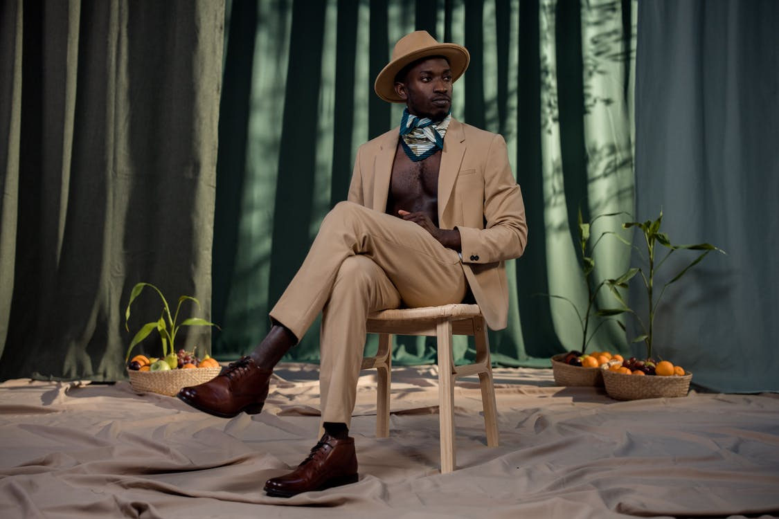 Man in Brown Suit Sitting on Brown Wooden Chair