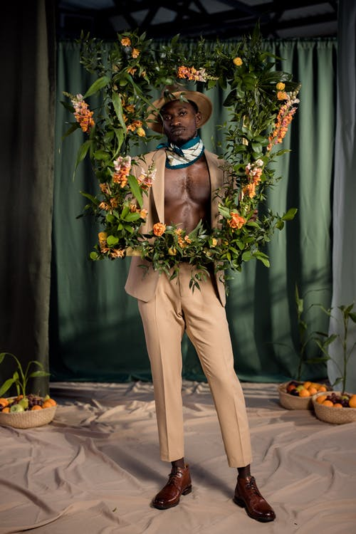 Man in Brown Pants Holding Bouquet of Flowers