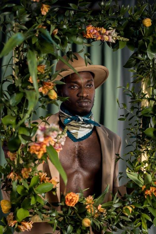 Man in Brown Cowboy Hat Standing Near Green Plants