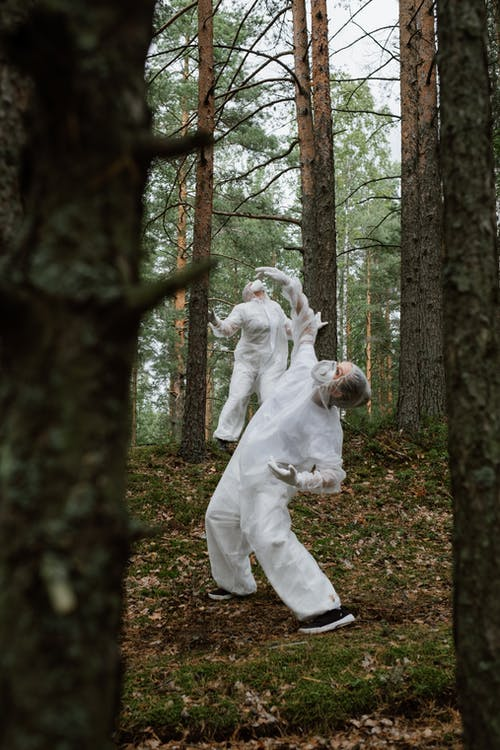 People Wearing Personal Protective Equipment Dancing in a Forest