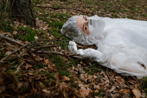 A Person Wearing Personal Protective Equipment Lying on the Ground
