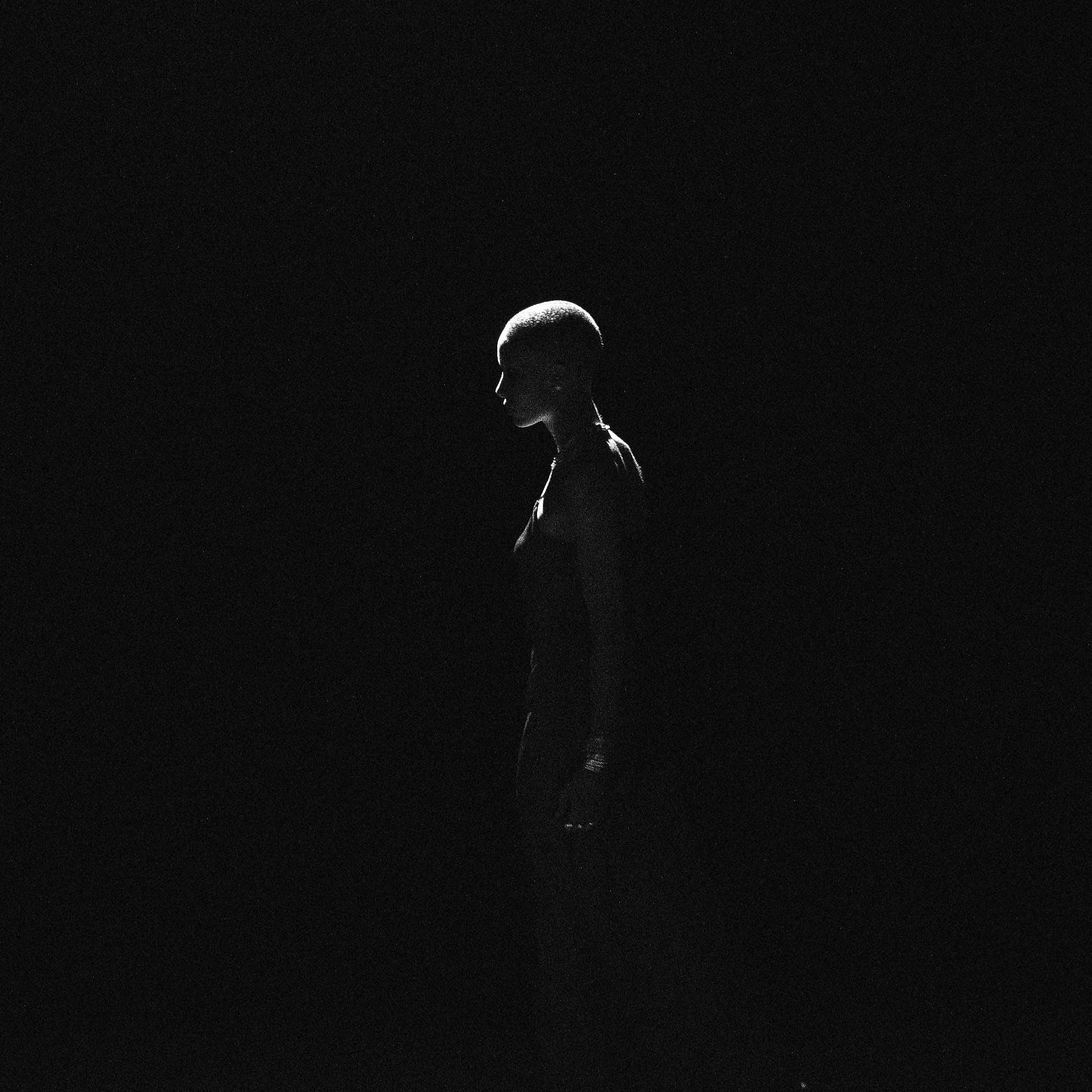 Kostenloses Stock Foto zu frau, licht, schwarzer hintergrund, seitenansicht