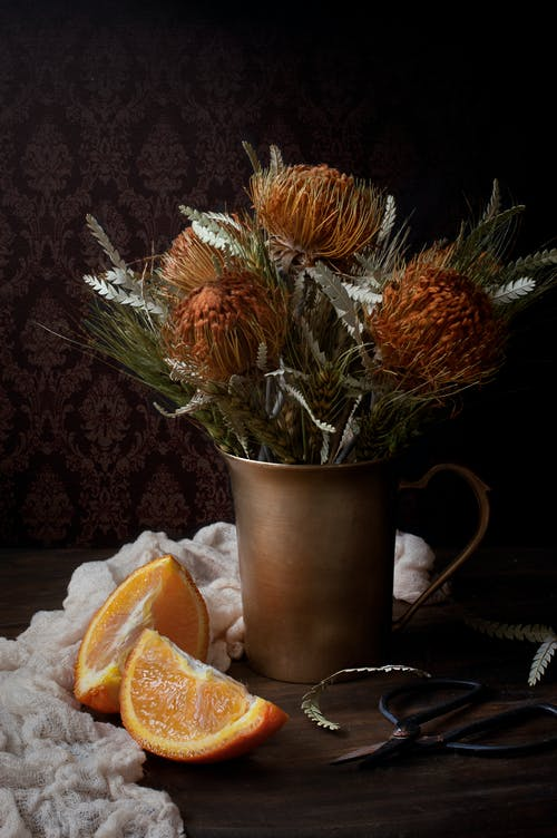 Orange Flowers in Brown Vase Beside Sliced Orange Fruit