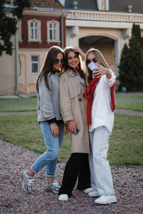 Full body of cheerful young female friends in casual outfits smiling and taking selfie on mobile phone while standing on street in city