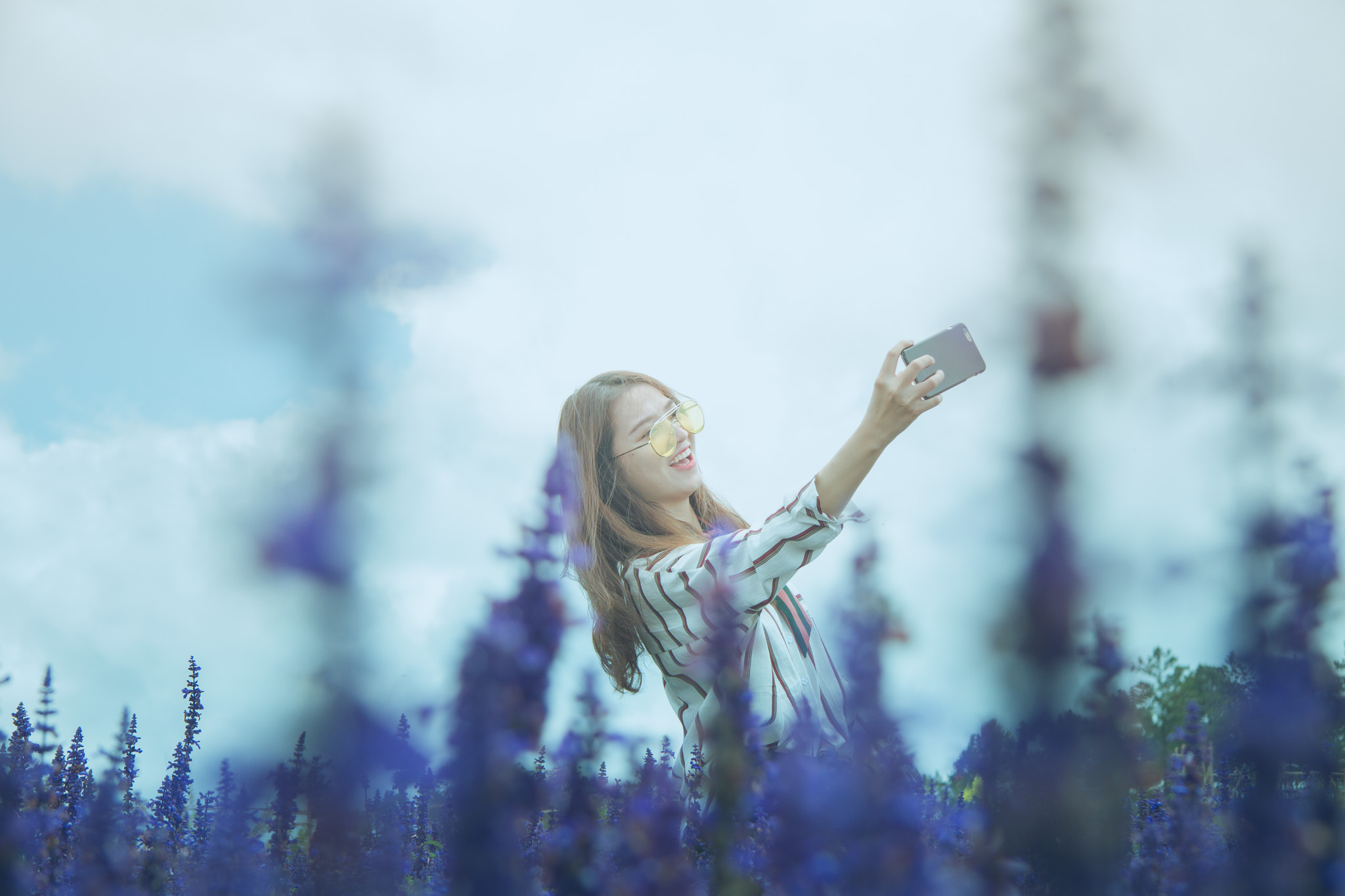 Woman in Black and White Dress Shirt Taking Photo on Lavender Flower Field at Daytime