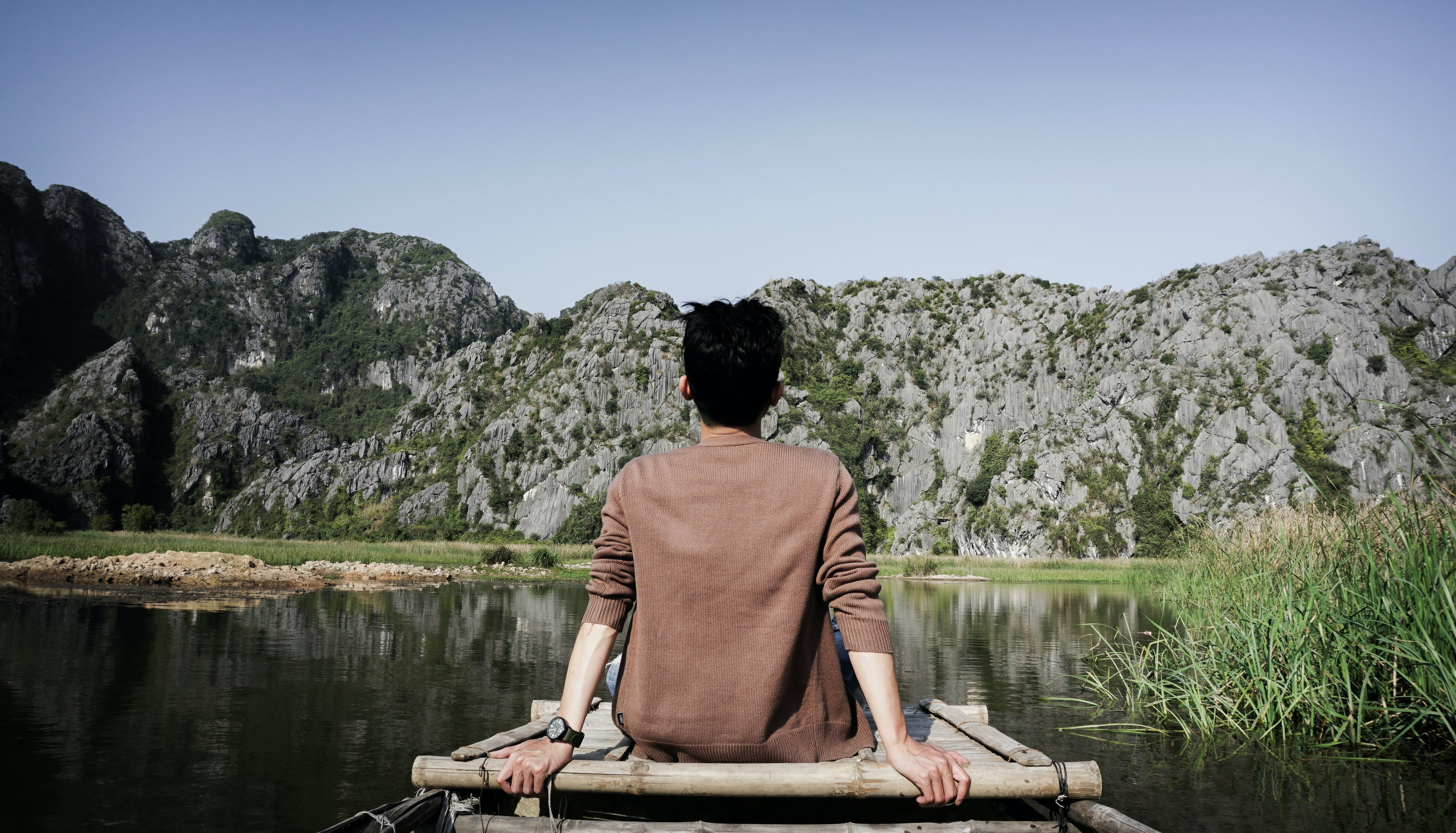 Man Sitting on Bridge Front of Mountain
