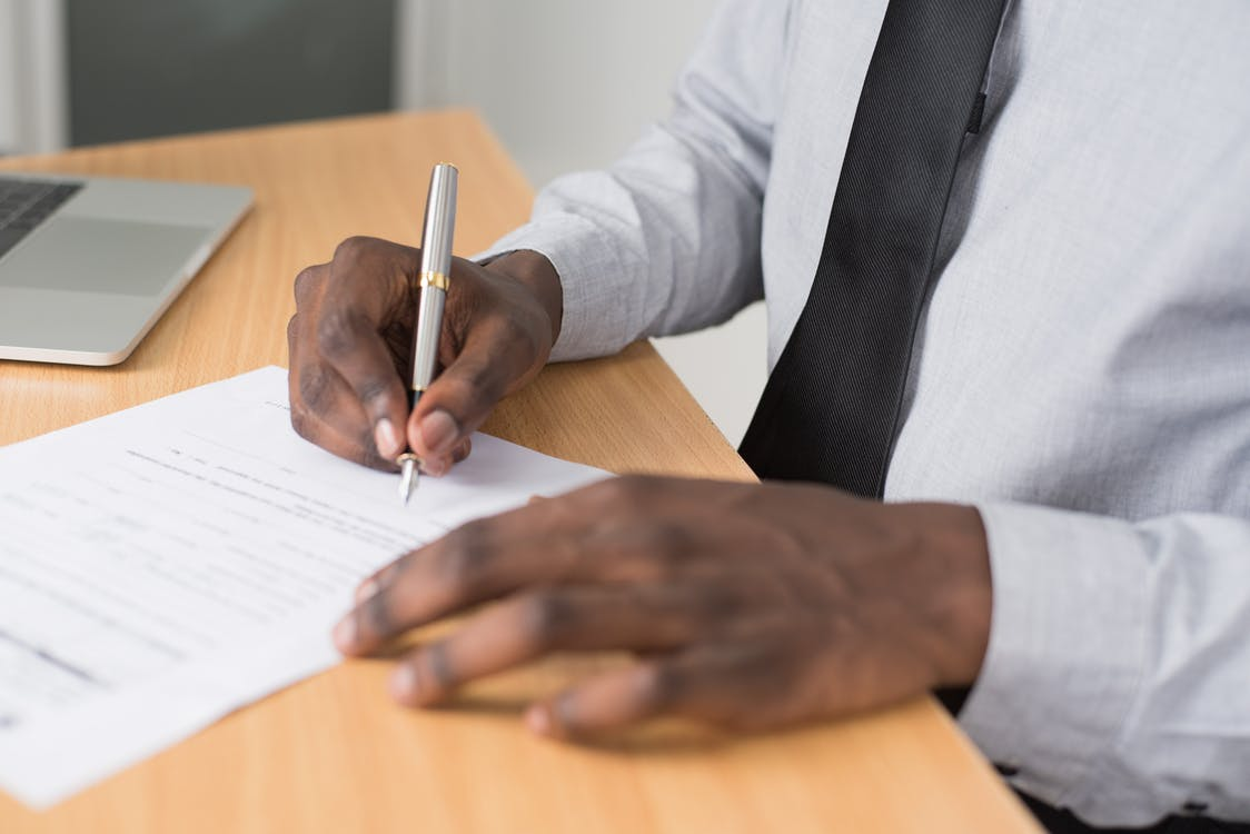 Person Wearing White Dress Shirt Signing Contract