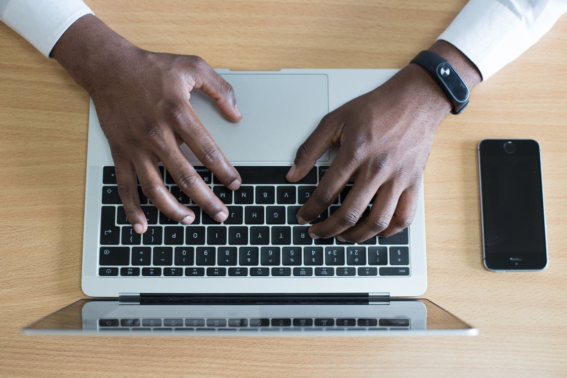 Closeup Photo of Person's Hands on Macbook Beside Space Gray Iphone 5s