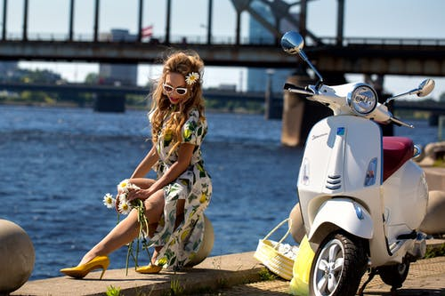 Woman in Green and White Floral Dress Sitting on White Motor Scooter