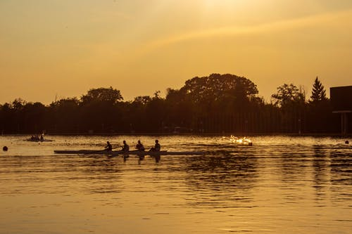Silhouette of People on Lake during Sunset