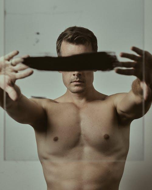 Topless Man Holding Black Textile