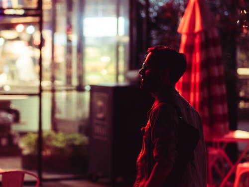 Man in Red Shirt Standing Near Window