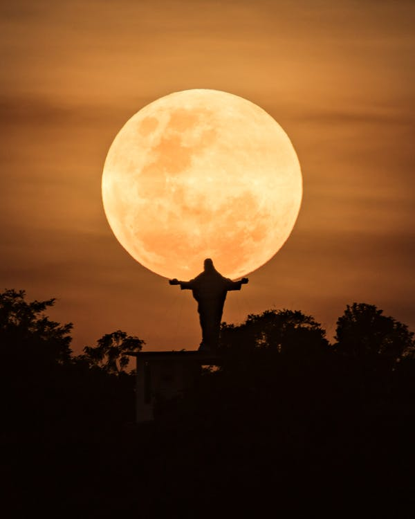 Silhouette of Man Standing on Top of Building Under Full Moon