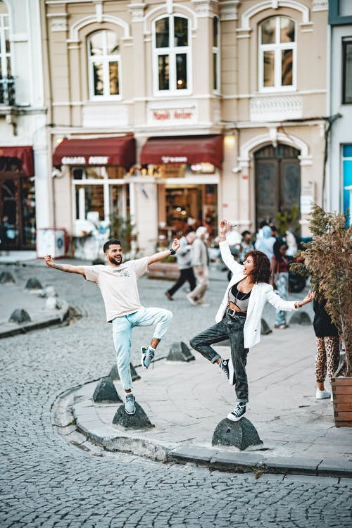 Man in White Shirt and White Pants Doing Stunts on Street