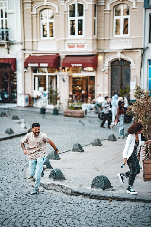 Man in White T-shirt and Gray Pants Running on Street