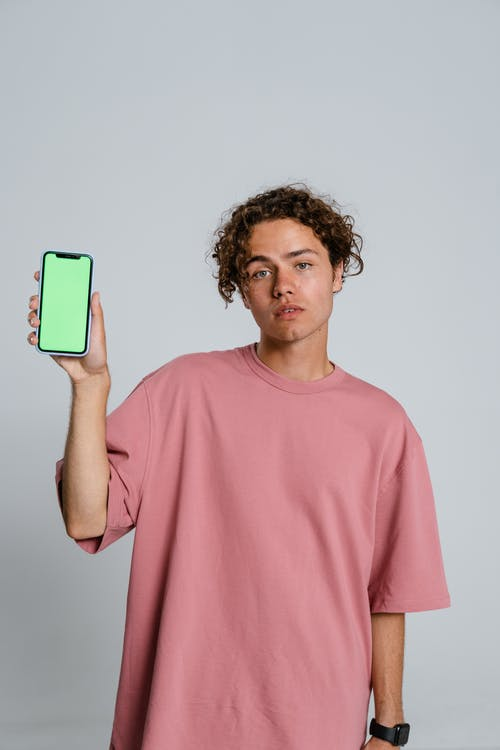 Man in Pink Crew Neck T-shirt Holding Blue and White Iphone Case
