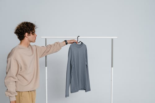 Man in Beige Long Sleeve Shirt Holding Gray Textile