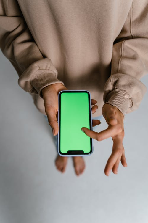 Person in Gray Sweater Holding White Iphone 5