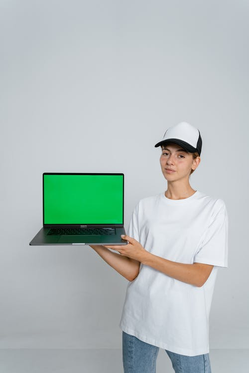 Woman in White Crew Neck T-shirt Holding Green Laptop Computer